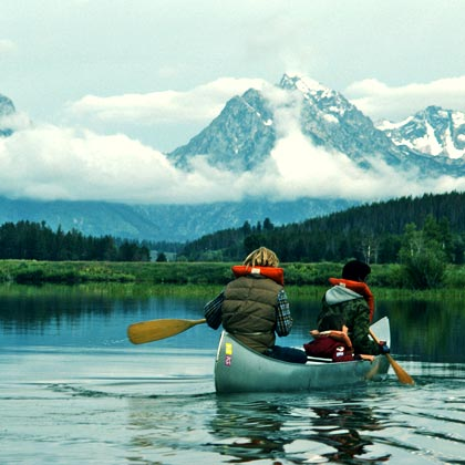 Three children in a canoe in a lake near Jackson Hole