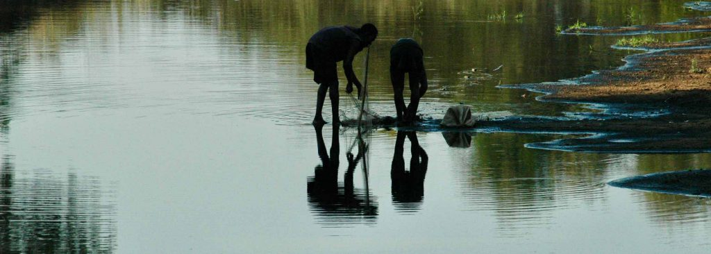 Two people examine a fishing net in the shallows of a river