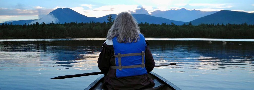 Back of a woman at the front of a canoe on a still lake, facing forested shoreline and distant mountains